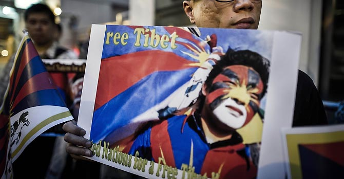 Rights groups activists stage a protest to raise awareness on the human rights situation in Tibet and the closure of the territory to foreign visitors, outside the Chinese liaison office in Hong Kong on June 20, 2012.  Since March 2011, 37 people have set themselves on fire in Tibetan-inhabited areas of China in protest at repressive government policies, according to activists. On May 27, two Tibetan men set themselves alight in front of the Jokhang temple, a renowned centre for Buddhist pilgrimage in the centre of Lhasa -- the first such incident to hit the regional capital. AFP PHOTO / Philippe Lopez
