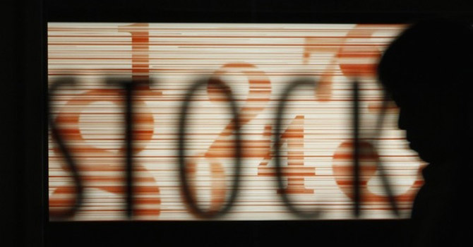 "A man passes by the word ""stock"" at the Tokyo Stock Exchange.—Reuters Photo"