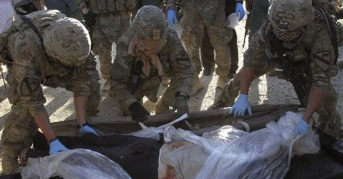 US soldiers with the NATO-led Isaf wrap the body of a comrade.—AP Photo