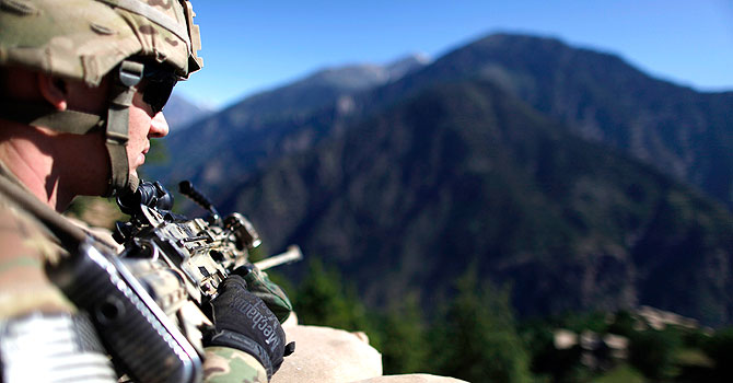 A United States' Army soldier from Charlie Company, 1-12 Infantry, 4th Brigade, 4th Infantry Division, keeps guard at Blocking Position one above Kamdesh in Afghanistan's Nuristan Province. – Photo by Reuters