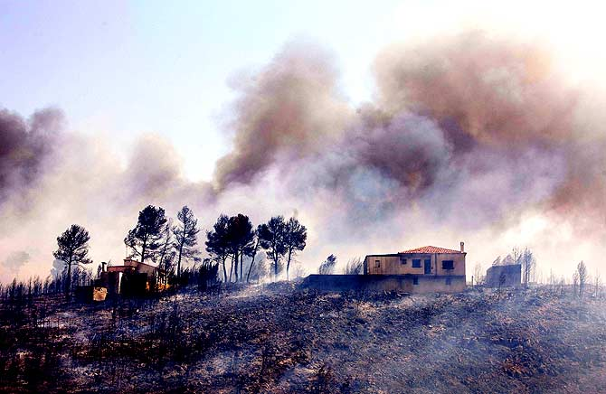 A view of a burnt house with smoke billowing in the background after the passage of a wildfire in Yatova, near Valencia on June 30, 2012. A forest fire in eastern Spain forced 700 people to evacuate their homes and indirectly caused a brief power cut at a nuclear plant, authorities said. The fire had burned 10 square kilometres of land in the Valencia region. ? Photo by AFP