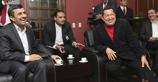 Venezuela's President Hugo Chavez (R) and Iran's President Mahmoud Ahmadinejad laugh as they watch TV during a visit at Miraflores Palace in Caracas June 22, 2012. REUTERS/