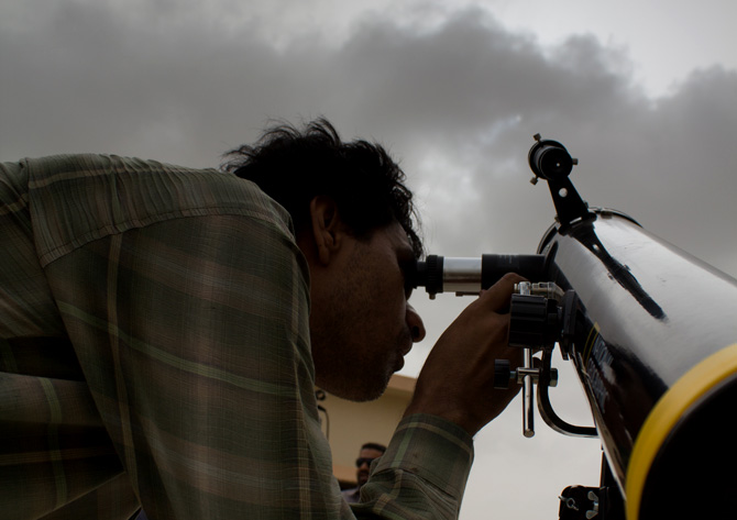 Rashid Ibrahim, a Ph.D student at ISPA looks through a telescope hoping to catch the the Venus transit on a cloudy day in Karachi. - Photo by Sara Faruqi/Dawn.com