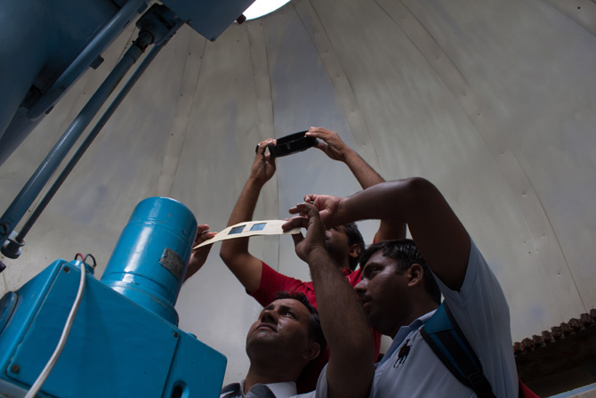 Students of the Institute of Space and Planetary Astrophysics (ISPA) at the Karachi University look up at the sky to see Venus travelling over the sun. - Photo by Sara Faruqi/Dawn.com