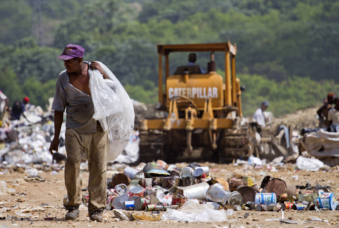 A scavenger collects plastics and other useful things at a dump in Haina, a town in southern Dominican Republic, on the eve of World Environment Day. ? Photo by AFP