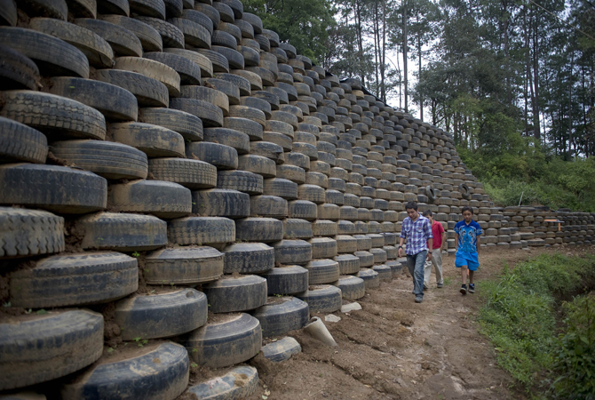 Children walk along a wall built with tyres by members of the 'Long Way Home' Organization which promotes building with recyclable materials for the care of the environment in San Juan Comalapa municipality, 82 km from Guatemala City. ? Photo by AFP