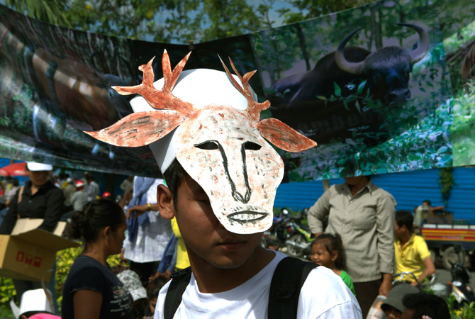 A Cambodian environmental activist wears a mask symbolizing a wild animal as he stands in front of a banner during a rally to mark World Environment Day in Phnom Penh, Cambodia. ? Photo by AP