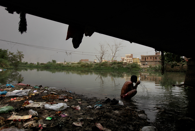 An Indian man bathes in a polluted channel under a bridge in Amritsar. ? Photo by AP