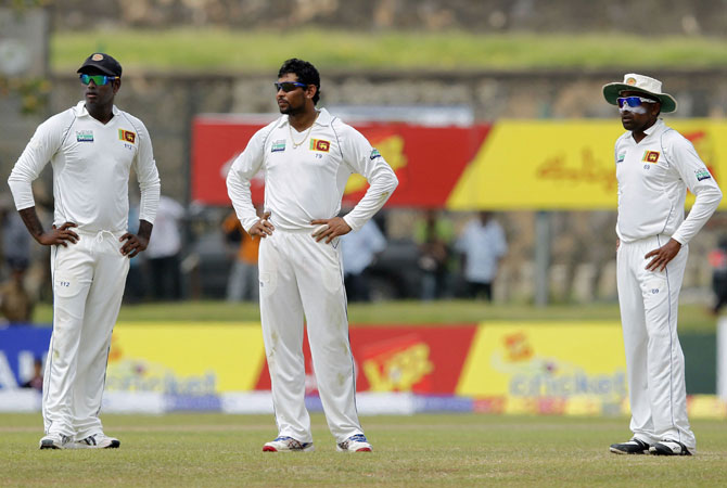 Sri Lanka's captain Mahela Jayawardene (R), vice-captain Angelo Mathews (L) and Tillakaratne Dilshan look at the third umpire box while they react after Pakistan's batsman Younis Khan was adjudged not out to a catch by Dilshan. -Photo by Reuters