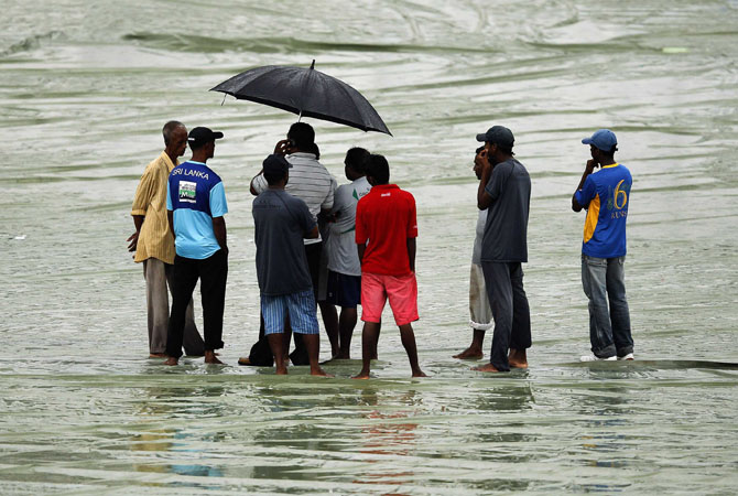 Ground workers stand on covers as the match was called off for the day due to rain, during the second day of second test match between Sri Lanka and Pakistan in Colombo July 1, 2012. ? Photo AFP