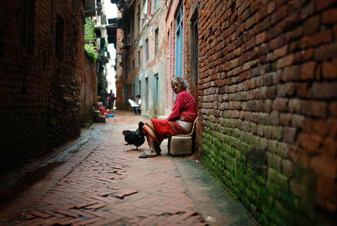 A woman sits outside her house in the ancient city of Bhaktapur, near Kathmandu. ? Photo by Reuters