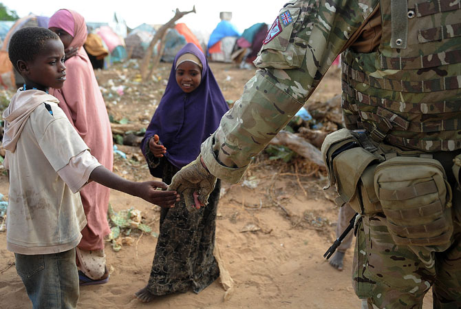 A Somali boy greets a British Army soldier in Afgoye, 30km from the capital Mogadishu on July 24, 2012. Afgoye was seized by African Union (AU) and government forces in late May from Al-Shebab insurgents; it was called the biggest concentration of displaced people in the world. Somalia has been embroiled in a civil war since 1991, when former president Mohamed Siad Barre was ousted. It has been variously governed by ruthless warlords, militia groups and a fragile transitional government which holds official power i
