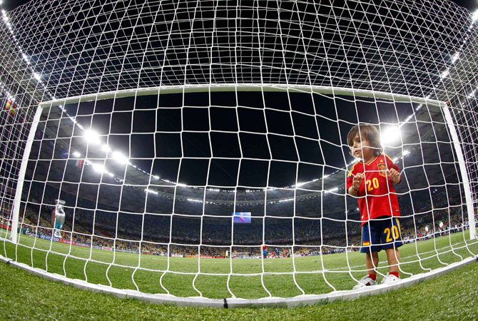 A child wearing Spain's Santi Cazorla's jersey stands in the net after the Euro 2012 final match. ? Photo by Reuters