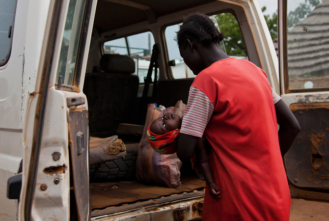 A woman carrying her sick child climbs into an International Rescue Committee (IRC) vehicle to travel to the Aweil State Hospital in Aweil from the Malualkon Primary Health Care Center in Malualkon, in the South Sudanese state of Northern Bahr el Ghazal. – Photo by Reuters