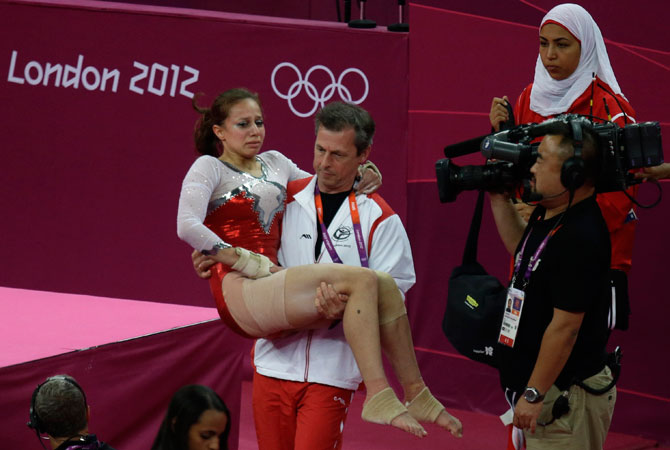 Egypt's gymnast Sherine Ahmed Elzeiny is carried by her coach after she sustained an injury during the Artistic Gymnastic women's qualifications at the 2012 Summer Olympics, Sunday, July 29, 2012, in London. ? Photo by AP