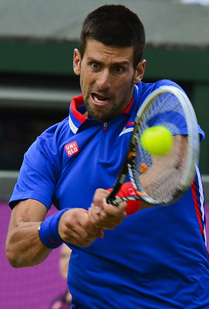 Serbia's Novak Djokovic returns to Italy's Fabio Fognini during their London 2012 Olympic Games men's singles tennis match first round at the All England Tennis Club in Wimbledon, southwest London, on July 29, 2012. ? Photo by AFP