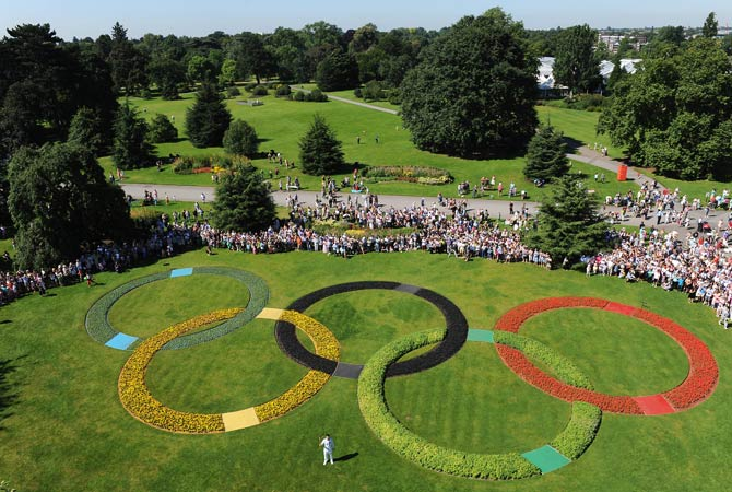 In a handout image released by the London 2012 Organizing Committee of the Olympic Games (LOCOG) on July 24, 2012 a torchbearer poses with the Olympic Flame on a Torch Relay leg for the London 2012 Olympic Games in front of the Olympic Rings at Kew Gardens in London. The London Games open on July 27. Photo by AFP