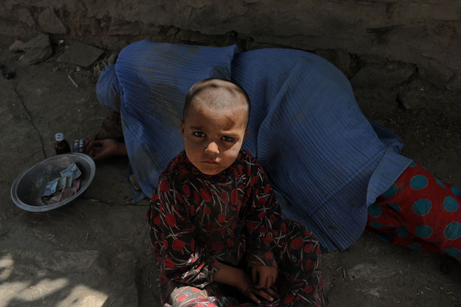 An Afghan woman begs while her child looks on at the roadside in Kabul on July 31, 2012 during the Islamic month of Ramadan. Throughout the month devout Muslims must abstain from food, drink and sex from dawn until sunset when they break the fast with the Iftar meal.  ? Photo by AFP