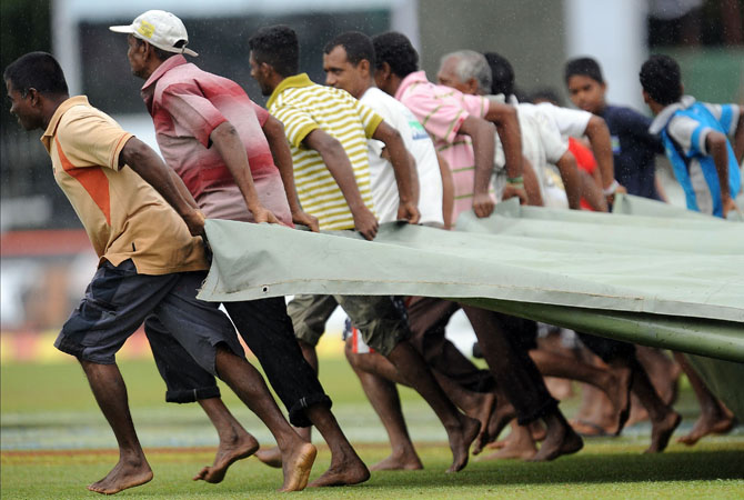 Sri Lankan ground staff pull a tarp over the grounds as rain stops play during the second day of the second Test match between Sri Lanka and Pakistan at the Sinhalese Sports Club (SSC)  in Colombo on July 1, 2012. ? Photo AFP