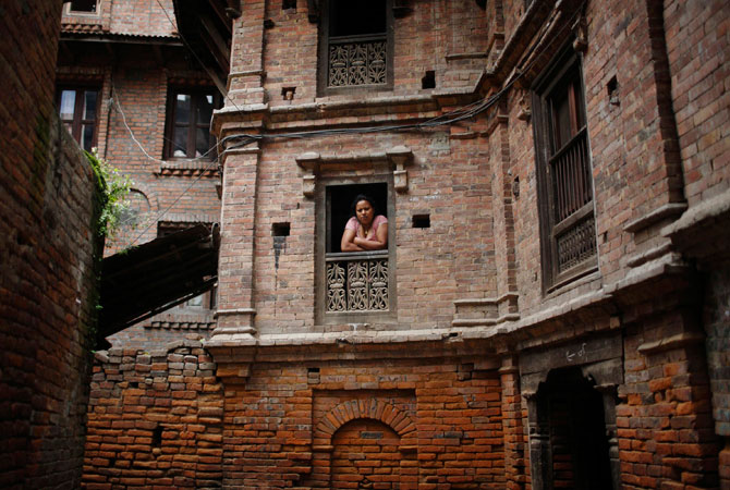 A woman looks out from the window of her house in the ancient city of Bhaktapur, near Kathmandu. ? Photo by Reuters