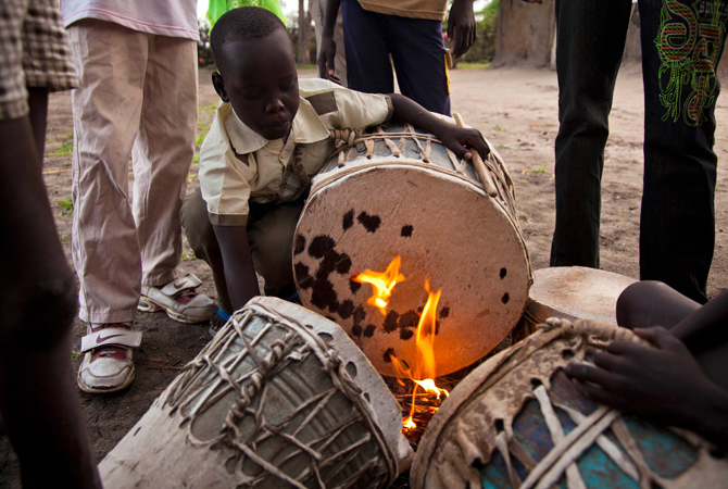 A boy tightens the hide on his drum before church services at the Presbyterian Church in Pibor. – Photo by Reuters