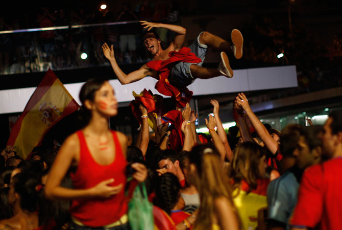 A fan (top) is tossed in the air by fellow Spain supporters as they celebrate Spain's victory over Italy in their Euro 2012. ? Photo by Reuters