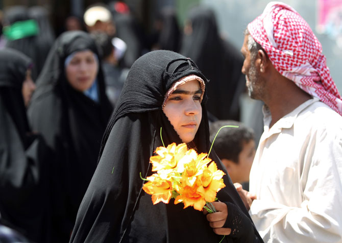 A Shiite pilgrim holds flowers in her hands as she tours the Imam Hussein shrine in the central Iraqi holy city of Karbala on July 5, 2012. The grandson of Islam's Prophet Mohammed is revered by Shiite Muslims across the world. ? Photo by AFP