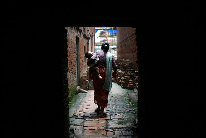 A woman carries a sleeping child as she walks through a small alley in the ancient city of Bhaktapur. ? Photo by Reuters