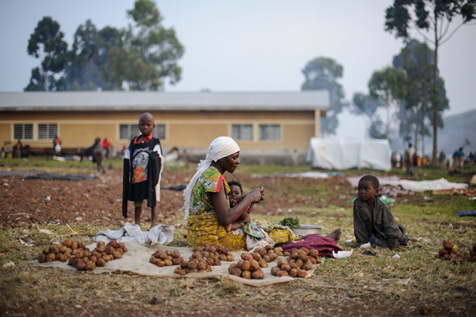 A displaced Congolese woman from Rugari sits peeling potatoes at a small stall she has set up in the Kanyarucinya primary school in Kibati district on the outskirts of Goma in the east of the Democratic Republic of the Congo on July 30, 2012. According to Prudent Mutarutwa, the secretary of the displaced camp here, over 11,000 people have come to Kanyarucinya in the past week, with over 20,000 people in Kabati district, fleeing fighting between the government army and M23 rebels in the area around Kibumba and Rugar
