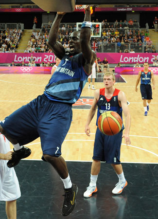 British forward Pops Mensah-Bonsu, left, hangs on the hoop after scoring during the men's group B basketball match against Russia at the 2012 Summer Olympics on Sunday, July 29, 2012, in London. ? Photo by AP