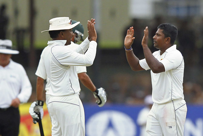 Sri Lanka's Rangana Herath (R) celebrates taking the wicket of Pakistan's Younis Khan with Sri Lanka's captain Mahela Jayawardene during the second day of second test match in Colombo July 1, 2012. ? Photo Reuters