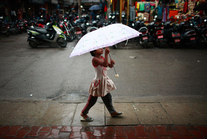 A girl walks with her umbrella along a street in Kathmandu. The monsoon season in Nepal typically lasts from June to August. ? Photo by Reuters