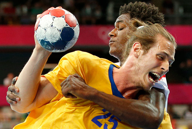 Sweden's Kim Ekdahl du Rietz, foreground is tackled by Tunisia's Wael Jallouz, background, in their men's handball preliminary match at the 2012 Summer Olympics, Sunday, July 29, 2012, in London. ? Photo by AP