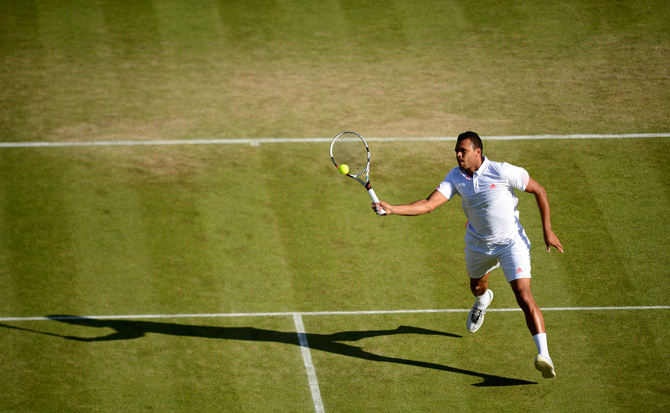 France's Jo-Wilfried Tsonga plays a forehand shot during his third round men's singles victory over Slovakia's Lukas Lacko on day six of the 2012 Wimbledon Championships tennis tournament at the All England Tennis Club in Wimbledon. ? Photo by AFP