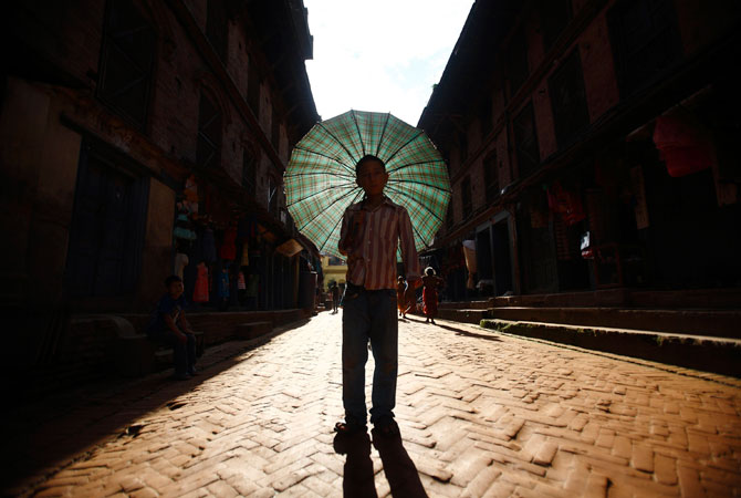 A boy with his umbrella arrives to participate for the Ghantakarna festival at the ancient city of Bhaktapur. According to legend, the demon is believed to 'steal? children and women from their homes and localities. ? Photo by Reuters