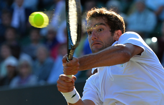 Croatia's Marin Cilic plays a double-handed backhand shot during his third round men's singles match against US player Sam Querrey on day six of the 2012 Wimbledon Championships. ? Photo by AFP