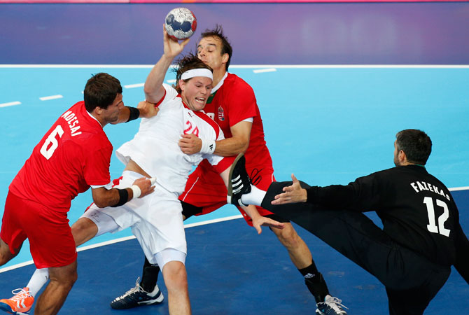 Denmark's Mikkel Hansen tries to shoot from between Hungary's Tamas Mocsai, left, and Attila Vadkerti, right, as goalkeeper Nandor Fazekas, right approaches during their men's handball preliminary match at the 2012 Summer Olympics, Sunday, July 29, 2012, in London. ? Photo by AP