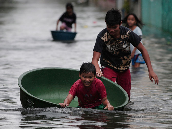 A Filipino boy plays along a flooded street in Obando town, Bulacan province, north of Manila, Philippines Tuesday July 31, 2012. Typhoon Saola dumped torrents of rain as it swept past the Philippines, killing at least seven people and displacing more than 20,000 others by Tuesday. ? Photo by AP