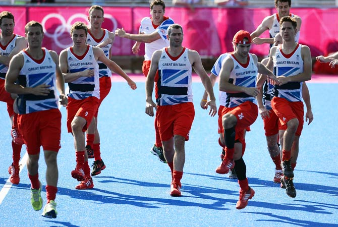 Members of Great Britain's men's hockey team warm-up during a training session at the Old Loughtonians Hockey Club at Chigwell on the outskirts of London on July 24, 2012 three days before the official start of the London 2012 Olympic Games. Photo by AFP
