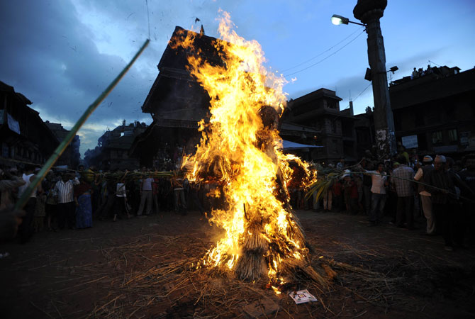 Nepalese people watch as a straw effigy of Ghanta Karna burns during celebrations of the Hindu festival of ?Gathemangal?, also known as Ghanta Karna, in Bhaktapur. The Nepalese festival, which celebrates the defeat of the mythical demon Ghanta Karna (?bell-ears?), is celebrated by performing the legendary drama in the streets. ? Photo by AFP