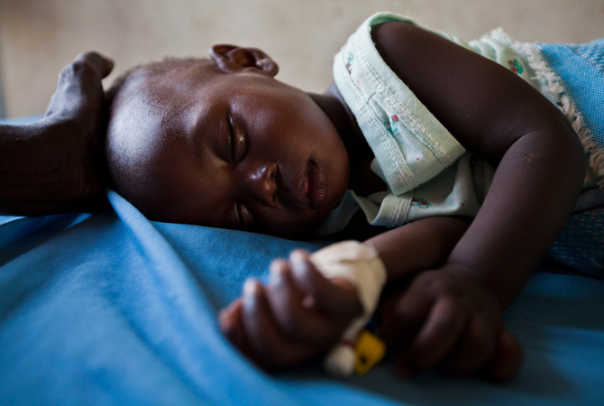 A young girl with malaria rests in the inpatient ward of the Malualkon Primary Health Care Center in Malualkon. Development experts have grown more sophisticated in recent decades about how they deliver aid. – Photo by Reuters