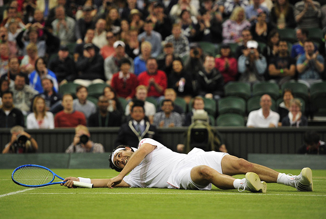 Cyprus's Marcos Baghdatis lies on the court after slipping during the fourth set of his third round men's singles match against Britain's Andy Murray on day six of the 2012 Wimbledon Championships. ? Photo by AFP