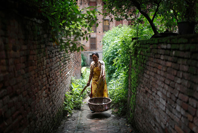 A woman collecting garbage walks though a small alley in the ancient city of Bhaktapur. ? Photo by Reuters