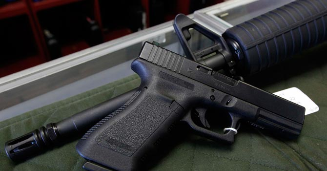 A Glock 22 pistol is seen laying on a Palmetto M4 assault rifle at the Rocky Mountain Guns and Ammo store. — AP Photo