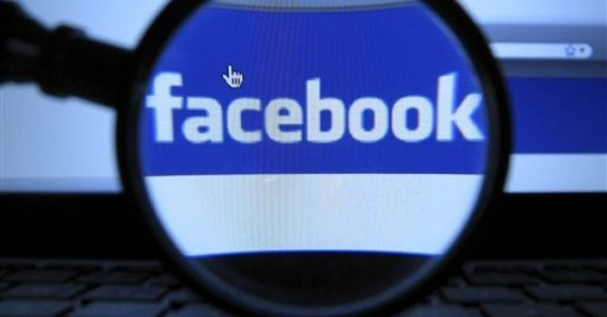 A magnifying glass is posed over a monitor displaying a Facebook page.—AP Photo