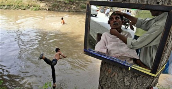 A Pakistani man is reflected in the mirror of a street barber while having a haircut, as a youth jumps in to a canal to cool off, in Lahore.—AP Photo