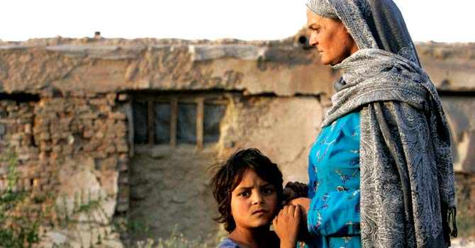 Afghan refugee Shapera, right, stands with her daughter Deevya near their house in a refugee camp built inside a civil war damaged government building in Kabul. – File photo by AP