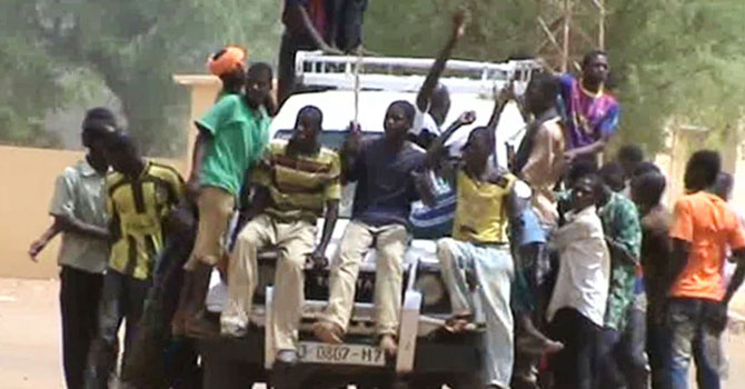 "A still from a video shows civilians riding on a 4x4 car shouting ""Allah Akhbar"" in the streets of Gao on June 27, 2012. Algerian jihadists arrived in Gao on June 29, 2012 to reinforce Islamist fighters in the northern Mali city after they chased Tuareg rebels from the town they had jointly occupied for three months, sources said. The Islamist group which drove out the Tuareg in fighting that caused 20 deaths, the Movement for Oneness and Jihad in West Africa (MUJAO), along with AQIM and Ansar Dine (Defenders of Faith) have taken firm control of Mali's vast north.  Ansar Dine leader Iyad Ag Ghaly arrived in the town on June 28, after the fighting a day earlier erupted between the Tuareg and Islamists resulted in the desert nomads being dislodged from all key positions in the city.     AFP PHOTO"