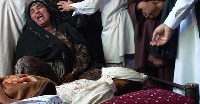 An Afghan woman cries over the dead body.—AFP Photo