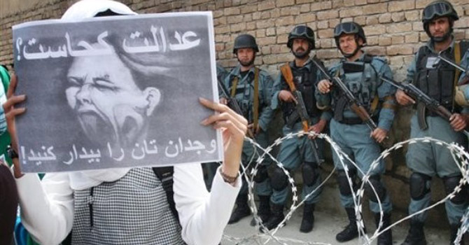 An Afghan woman holds up a poster during a protest.—AP Photo